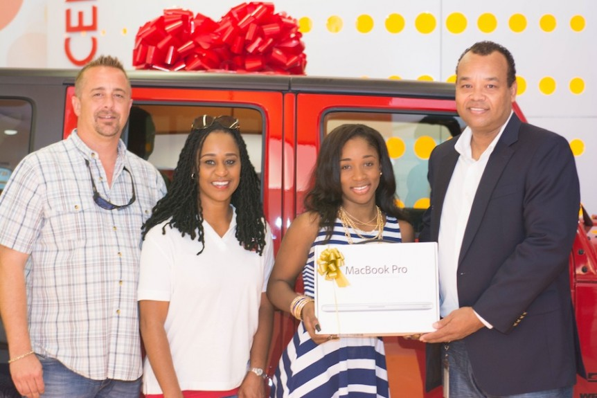"Nassau resident Terrell Neely (second right) was randomly selected as the first winner in Cable Bahamas' ""12 Days of Giveaways"" drawing and received a brand new Apple MacBook Pro as her prize"