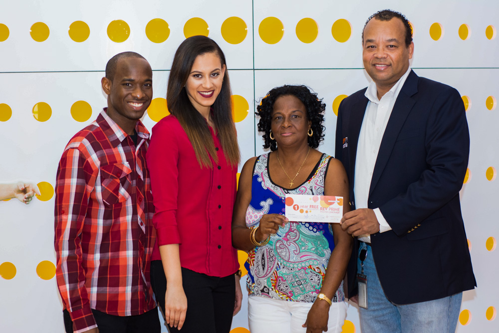 """Cable Bahamas representatives award and winning customer in the """"12 Days of Giveaways"""" promotion"""